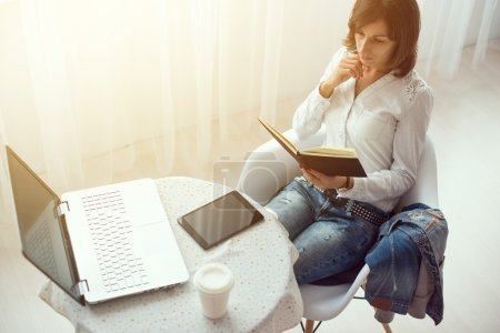 Businesswoman with laptop and diary in a bright office