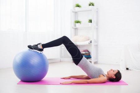Sporty woman doing pilates exercise lifting her pe...