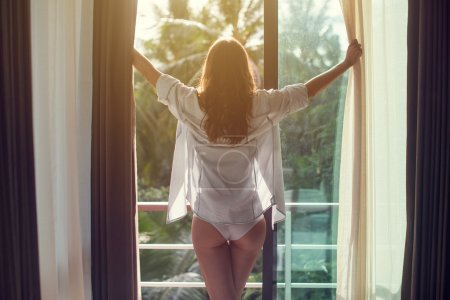 Photo for Lovely woman is awoke and standing before window. Girl is opening curtains and meeting sunrise - Royalty Free Image