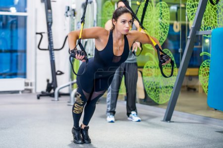 Girl doing exercises with trx at gym