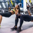 Woman exercising with suspension straps in fitness...