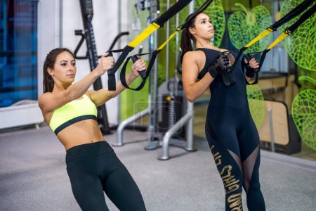 Woman exercising with suspension straps