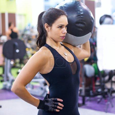 Photo pour Entraînement musculaire femme fit dans la salle de gym. Femme forte, faire des exercices avec médecine-ball en club de remise en forme - image libre de droit
