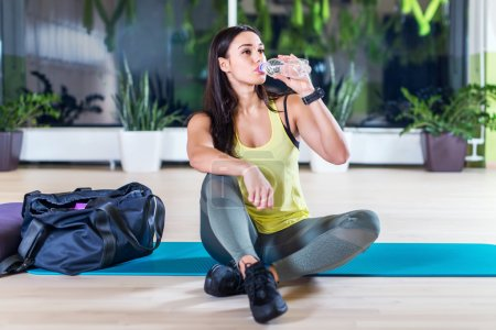 woman drinking water after training work