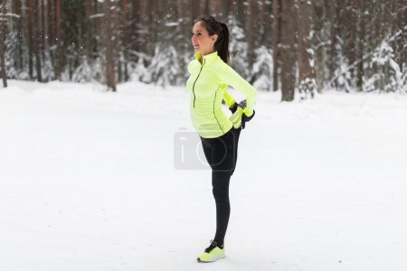 Photo for Fit young woman stretching her leg before a run in forest or park - Royalty Free Image