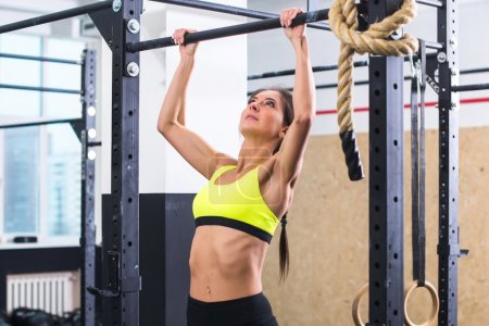 Photo for Athlete fit woman performing pull ups in a bar exercising at gym - Royalty Free Image