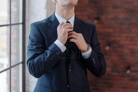 Photo pour Gros plan de l'homme d'affaires ajustant sa cravate debout dans le bureau - image libre de droit