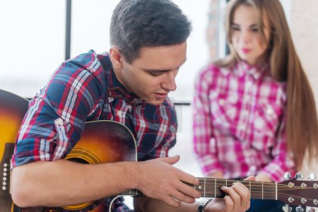 Young man singing playing guitar for his girlfriend