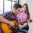 Young man singing playing guitar for his girlfrien...