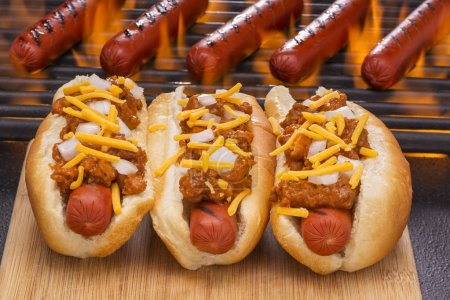 Three Chili Hot Dogs and Flaming Barbecue Grill Background