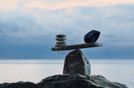 Photo for Symbol of scales is made of pebbles on the sea boulder - Royalty Free Image