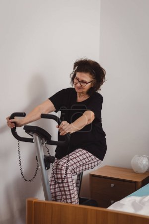 Photo for Beautiful and happy looking senior woman in mid 70's exercise on stationary bike in her bedroom. Active mature female. - Royalty Free Image