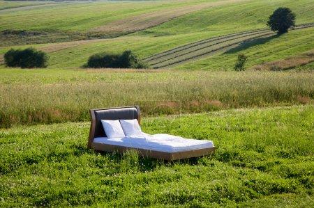 Photo pour Lit dans un champ d'herbe concept de bon sommeil - image libre de droit