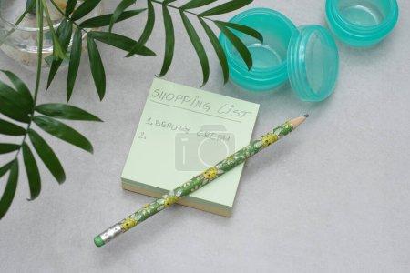 Une liste d'achats manuscrite sur A Post-it Sticky Notes.Vide pots sans marque pour crème de soins.Récipients en plastique vert sans étiquettes sur fond gris.Concept de planification cosmétique et shopping.