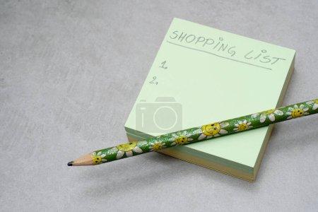 Une liste d'achats manuscrite sur A Post-it Sticky Notes. Vert carré forme note de service pad.Grey background.Organization concept. Concept de planification des achats.