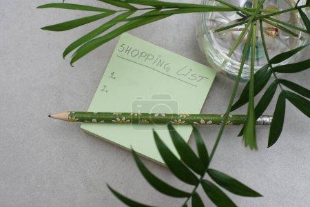 Une liste d'achats manuscrite sur A Post-it Sticky Notes. Feuilles vertes et fond gris.Concept d'organisation. Concept de planification des achats.
