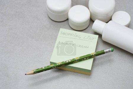 Une liste d'achats manuscrite sur A Post-it Notes. Flacons et bocaux en plastique blanc vierges pour les produits de soins de la peau sans étiquettes. Emballage de produits de beauté sans marque. Fond gris. Concept de planification des achats.