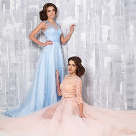 Two beautiful twins young women in luxury dresses, pastel colors. Beauty fashion portrait