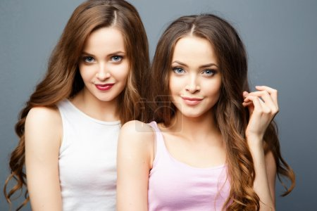 Beautiful twins young women in casual clothes over grey background. Beauty fashion portrait, casual style