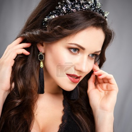 Elegant young woman with perfect makeup and hair style in a black dress with diadem and earrings. Beauty fashion portrait with accessories