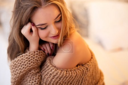 Photo for Young blonde woman in a warm pullover in a light bedroom in a morning - Royalty Free Image