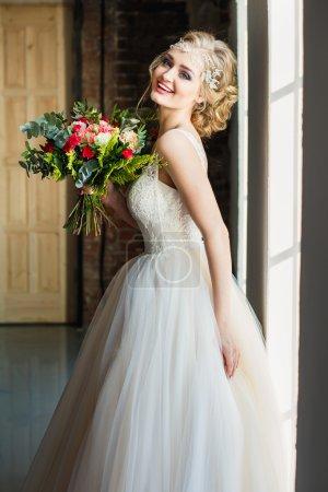 Photo pour Belle mariée dans le bouquet magnifique de fixation de robe de luxe dans un espace de grenier. Photo de mariage moderne - image libre de droit