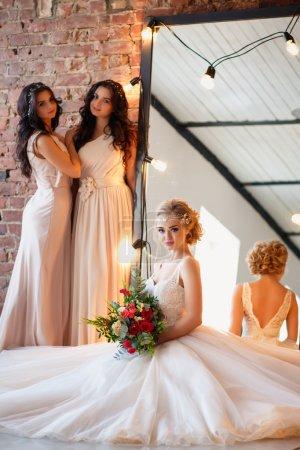 Photo pour Belle mariée blonde en robe de mariée de luxe et jolies demoiselles d'honneur jumelles dans des robes similaires le matin dans un espace loft avec un miroir et une guirlande de lampes. Mode moderne photo de mariage . - image libre de droit