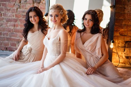 Beautiful blonde bride in luxury wedding dress and pretty twins bridesmaids in similar dresses in a morning in a loft space with a mirror and garland of lamps. Fashion modern wedding photo.