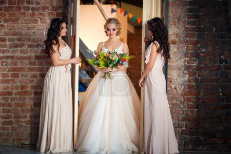 Photo pour Belle mariée blonde en robe de mariée de luxe et jolies demoiselles d'honneur jumelles dans des robes similaires le matin dans un espace loft. Mode moderne photo de mariage - image libre de droit