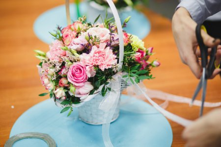Photo for Florist workplace: pretty bouquet in a basket on a background of flowers and accessories. soft focus - Royalty Free Image