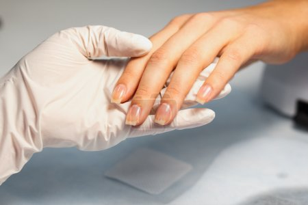 Manicure care procedure, Close-up photo Of Beautician Hand Filing Nails Of Woman In Salon