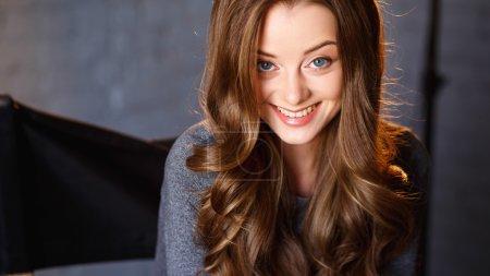 Photo pour Portrait émotionnel d'une jeune femme sensuelle aux longs cheveux bouclés et au maquillage naturel - image libre de droit