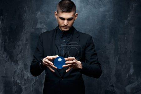Photo pour Magicien jeune homme dans un costume noir tient une sphère magique - image libre de droit