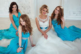 Bride and three bridesmaids in similar blue dresses with perfect make up and hair style in a light loft space