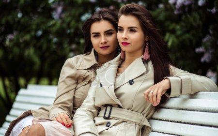 Photo pour Deux belles jeunes femmes en trench-coats près de floraison lilas des jumeaux - image libre de droit