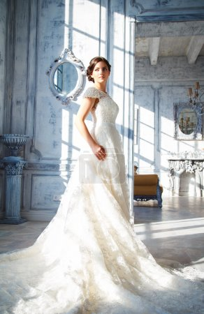 Photo for Photo of a beautiful brunette bride in a luxurious wedding dress in elegant expensive interior - Royalty Free Image