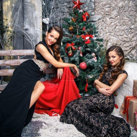 Photo pour Portrait de belles jumelles jeunes femmes en robes de soirée magnifiques sur fond de Noël - image libre de droit