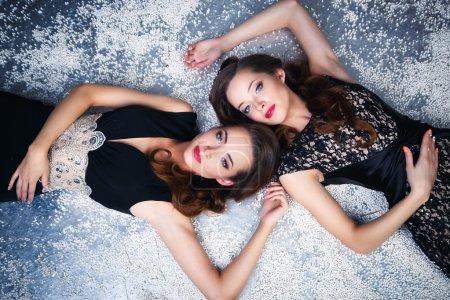 Photo pour Portrait de belles jumelles jeunes femmes en robes de soirée magnifiques allongées sur une neige - image libre de droit