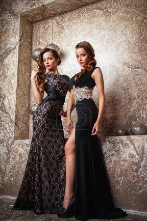 Photo pour Portarit de belles jumelles jeunes femmes en robes de soirée magnifiques - image libre de droit