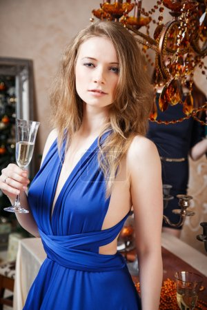 Portrait of beautiful young woman with glass of champagne celebrating new year with friends