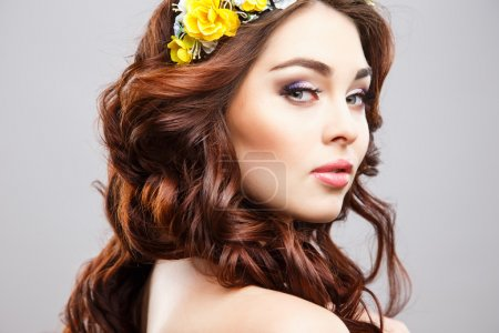 Close-up portrait of beautiful young woman with perfect make-up and hair-style with flowers in hair