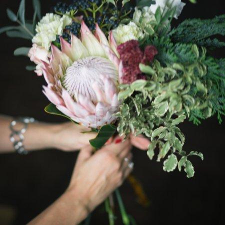 Photo pour Fleuriste au travail : jolie jeune femme blonde faisant bouquet moderne de différentes fleurs - image libre de droit