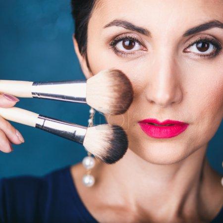Makeup. Make-up Face. Big Make up brush. Makeup applying concept. Beautiful strong woman face closeup. Skin tone. Facial powder