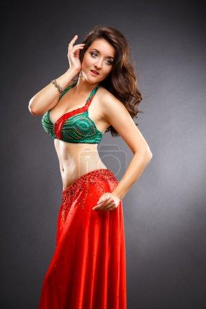 Photo pour Belle danseuse du ventre jeune femme en robe magnifique costume rouge et vert - image libre de droit