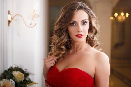 Photo pour Belle jeune femme avec un maquillage parfait et une coiffure en robe de soirée rouge magnifique dans un intérieur de luxe coûteux - image libre de droit