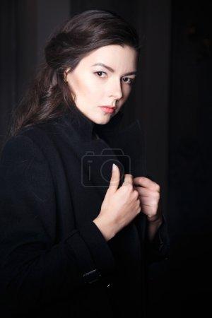 Foto de Retrato de mujer morena joven elegante abrigo largo negro y vestido en interior - Imagen libre de derechos