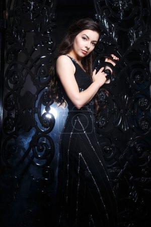 Photo pour Portrait de jeune femme brune élégante en robe de soirée noire longue à l'intérieur - image libre de droit