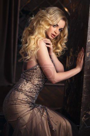 Photo pour Portrait de belle jeune femme aux cheveux dorés en robe de luxe à l'intérieur. Mode beauté portrait - image libre de droit