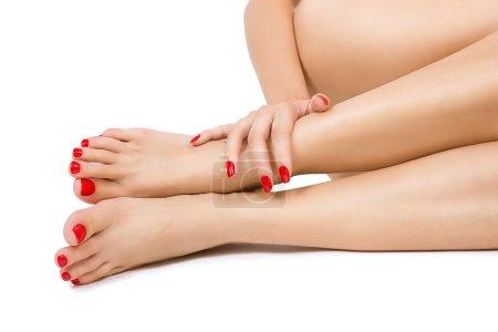 Photo pour Belles longue femmes sexy jambes nues avec pédicure rouge, femelle de ressuage avec pédicure rouge et des mains avec manucure rouge, proche place, isolé - image libre de droit