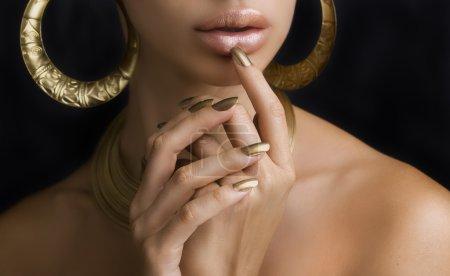 Photo pour Belles lèvres de femmes élégantes doré brillant rouge à lèvres et les mains avec manucure or et bijoux or sur fond sombre. Maquillage, mode, beauté. Voiture de l'ongle - image libre de droit